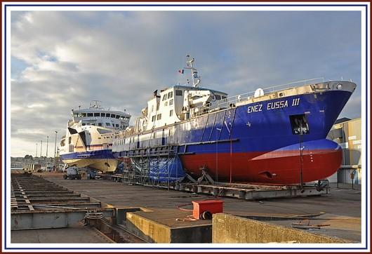 Deux bateaux à passagers sur l'air de travail du port de Concarneau. Tout au fond, on reconnait le Vindilis de la Compagnie Océane. Il assure la liaison maritime entre le continent (Quiberon) et Belle Ile dans le Morbihan. Au premier plan, il s'agit du Enez Eussa III, de la Compagnie Penn Ar Bed, qui assure la desserte quotidienne des îles d'Ouessant et Molène dans le Finistère. Ces deux bateaux sont à Concarneau pour des escales techniques (travaux de peinture pour Le Vindilis et réparation pour le Enez Eussa III). Photo prise le 22 janvier 2011.